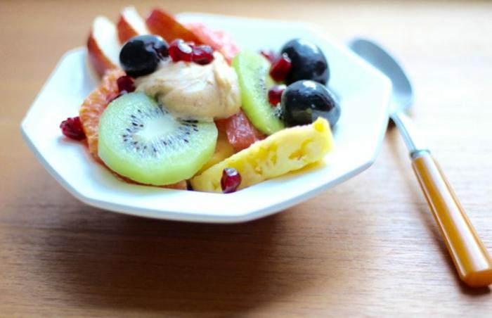 assiette blanche, salade de fruits saisonnières, ananas, raisins, kiwi, graines de grenade, fromage camembert, pommes