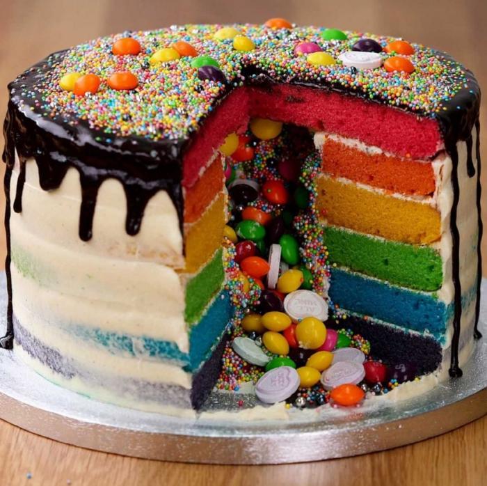 gâteau arc-en-ciel au glaçage coulant de chocolat et vermicelles avec un centre creux rempli de petites gourmandises
