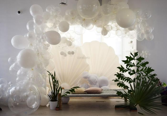 salle de séjour, arche de ballons blancs, plantes vertes, salon gris, grand coquillage blanc