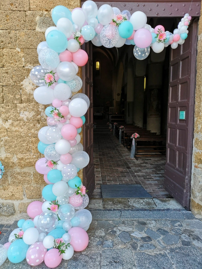arche de ballons décorés de jolies roses à l'entrée de l'église, banquettes décorées pour la cérémonie d'un mariage champêtre