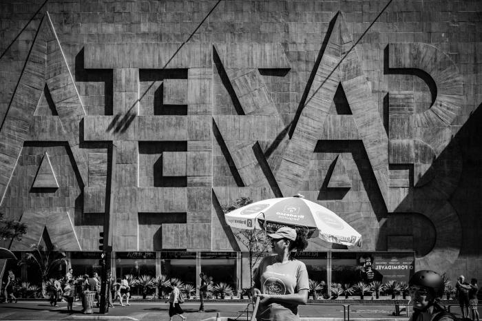 une photo noir et blanc femme dans la rue qui se tient devant la façade d'un bâtiment au brésil