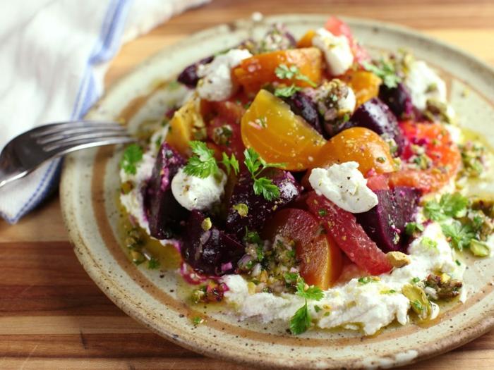 salade de fruits d'hiver originale, kakis et betterave rotie, salade chaude, fromage de chèvre, graines et herbes aromatiques