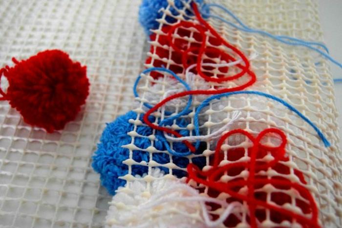 pompons attachés au dos d'une toile canevas, pompons rouges blancs et bleus combinés