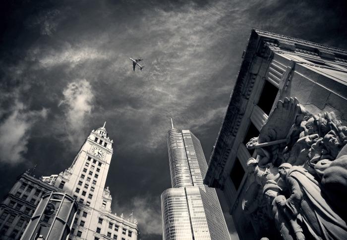 une belle image noir et blanc d'un avion volant au-dessus des bâtiments, photographie monochrome urbain