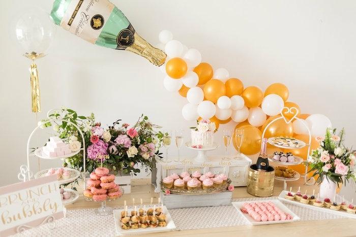 ballon bouteille de champagne, plusieurs ballons rassemblés qui sortent de la bouteille de champagne, ballons jaunes et blanches, bouchés sucrées apétissantes