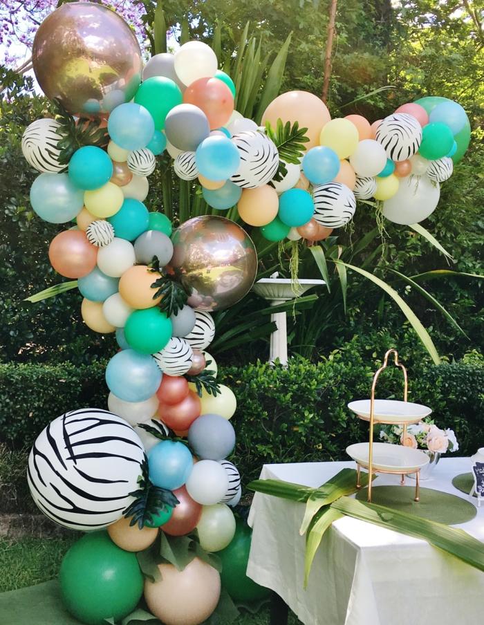 ballons pour un party de jardin, grande arche de ballons, haies vertes et plantes tropicales, table arrangée