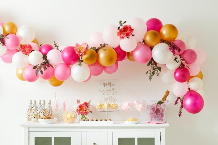 petite commode blanche, petites bouteilles arrangées, bouteille de champagne posée dans un récipient en verre plein de roses, arche faite avec ballons