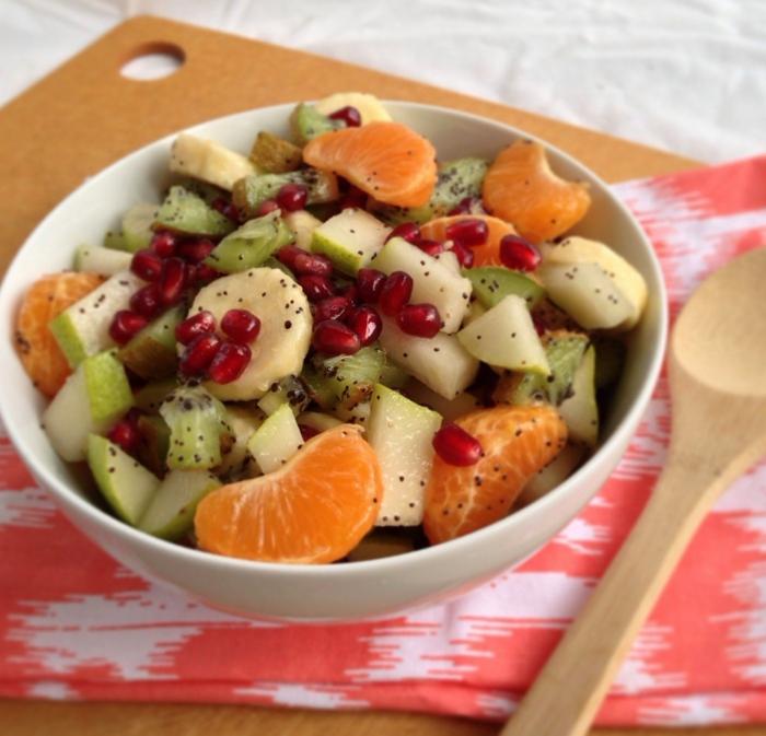 salade de fruits d'hiver, bananes et mandarines, graines de grenade, graines de pavot, kiwi, bol blanc, serviette rose et blanche, cuillère en bois
