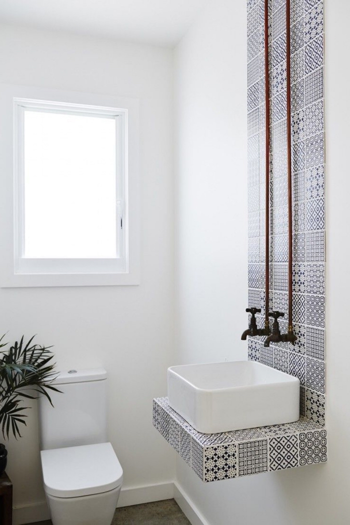 une bande de carreaux de ciment à motifs gris qui délimite la vasque et joue le rôle de crédence originale