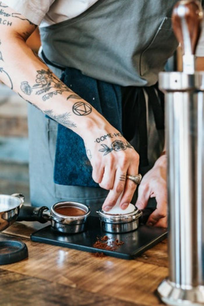 Tatouage géométrique, dessin artisrique pour un tatou magnifique, design original sur la peau d'un homme barista, tatouages stylés graphique manchette