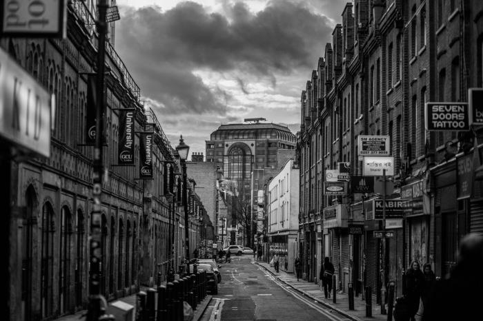 paysage noir et blanc urbain avec vue sur une rue bordée de bâtiments historiques sous le ciel ombrageux