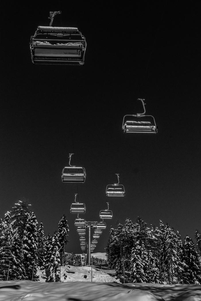 une belle image noir et blanc prise en dessous d'un téléphérique dans la montagne enneigée entre ciel et terre