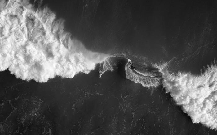 belle photo noir et blanc de surfeur et de bateau en plein océan dans du surfeur