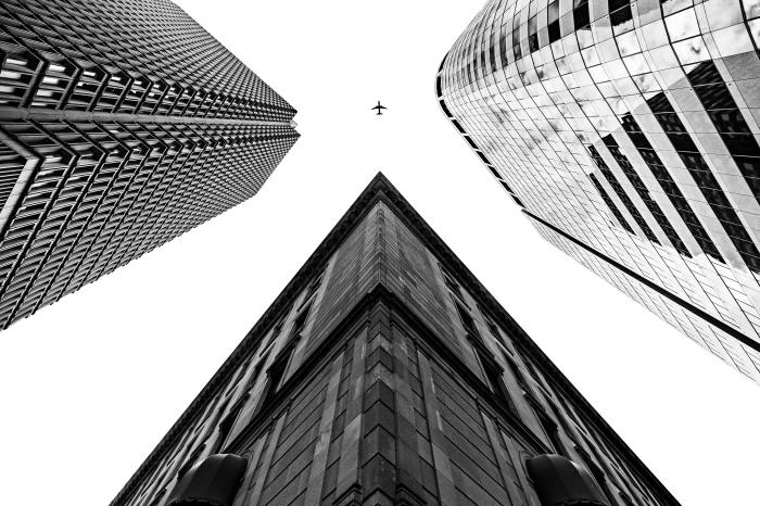belle photo noir et blanc d'un avion dans le ciel entre trois grands bâtiments, paysage urbain avec perspective originale