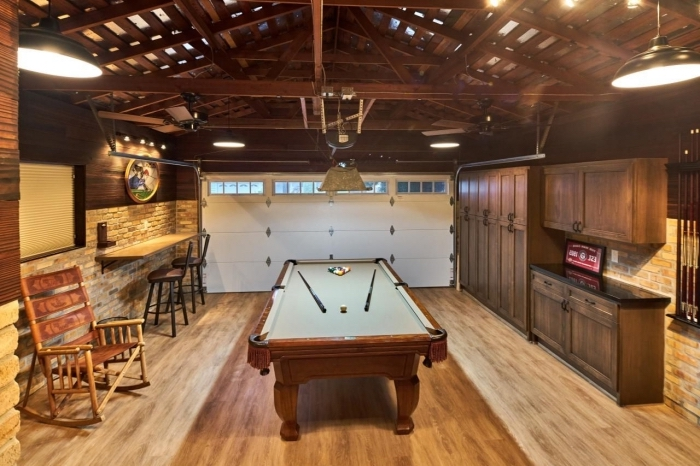 aménagement salle de jeux dans un garage, déco de style rustique avec murs en pierre et plafond de bois foncé