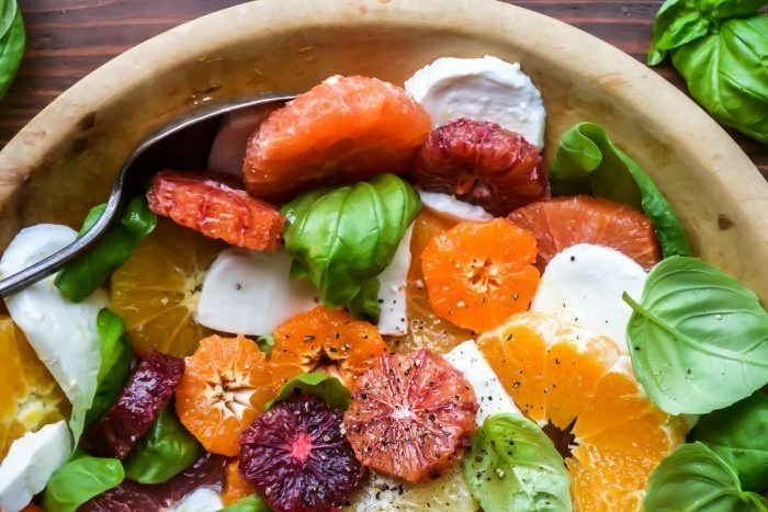 fromage de chèvre en rondins, agrumes, pamplemousse rose et rouge, orange tranchés en rondins, épinards et graines de pavot, grand bol de salade