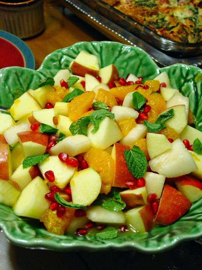 jolie salade de fruits d'hiver, pommes, poires, graines grenade, menthe, mandarines tranchées, dessert apétissant