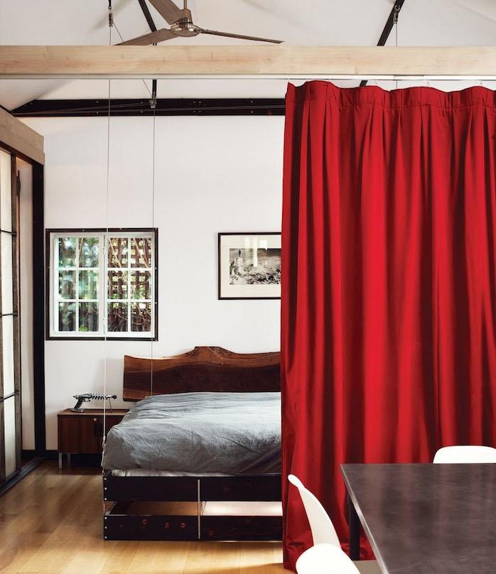 rideau separateur rouge idee de separation piece originale montée sur poutre apparente, lit suspendu avec matelas gris, parquet clair