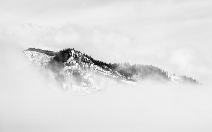 un paysage hivernal en noir et blanc de montagne enveloppée de brumes, photographie de paysage monochrome