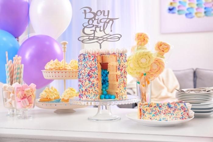 gateau a la vanille à plusieurs couches qui renferme des bonbons bleus en son centre creux, avec vermicelles colorées et un cake topper pour baby shower, buffet sucré de baby shower