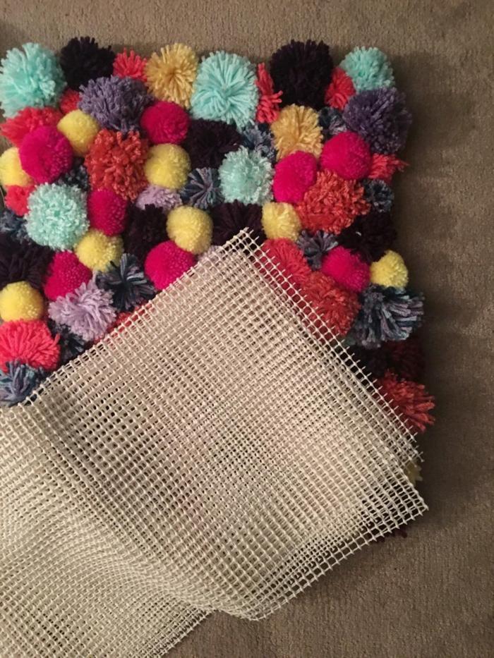 canevas blanc, tapis pompons plusieurs couleurs, pompons différente taille aux longs brins