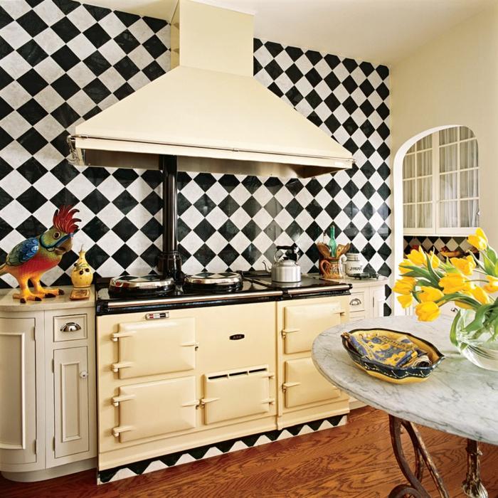 cuisine style country, table ronde marbrée, pieds en fer forgé, vase avec tulipes jaunes, crédence de cuisine damier