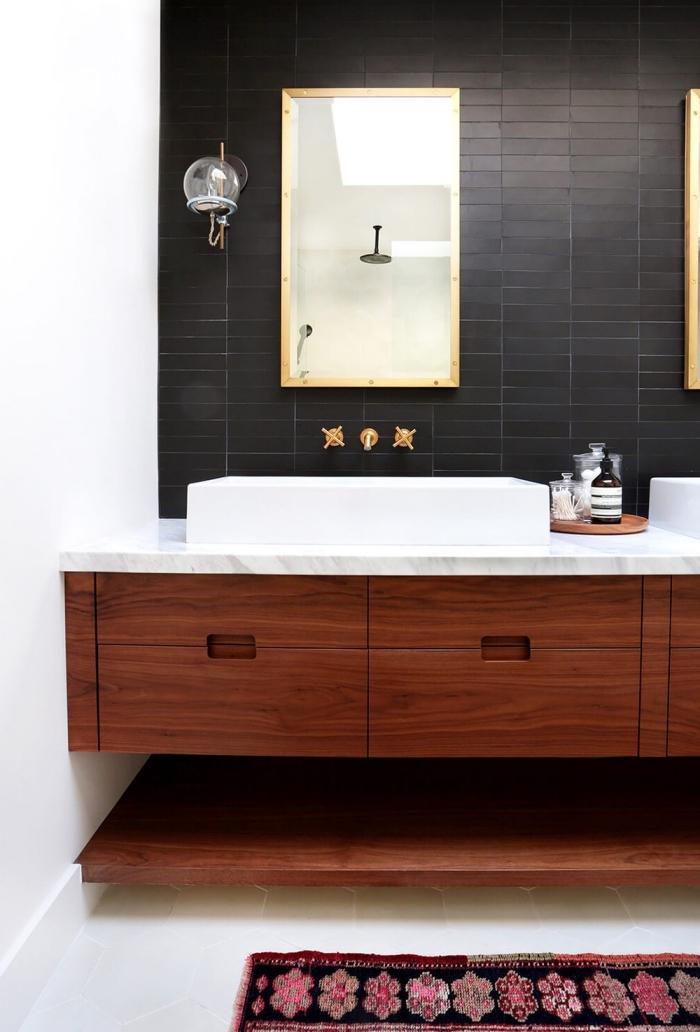 crédence de salle de bains en carrelage métro noir à finition mate qui s'élève jusqu'au plafond rehaussé par le robinet mural doré l'applique boule de verre