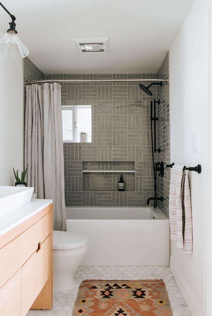 carrelage mural émaillé en gris vert qui habille les murs autour de la baignoire tout en délimitant l'espace douche
