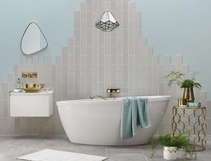 carrelage mural posé sur le mur derrière la baignoire d'un aspect inachevé, meuble sous vasque suspendu avec vasque à poser en laiton