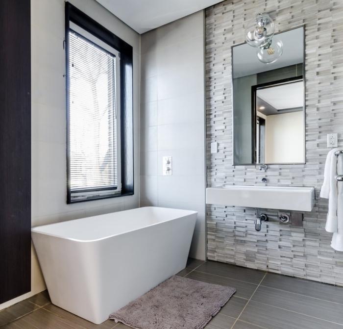 un panneau mural salle de bain en mosaïque imitation pierre posé en crédence derrière le lavabo qui donne tout l'intérêt à cette salle de bains moderne équipée de baignoire indépendante