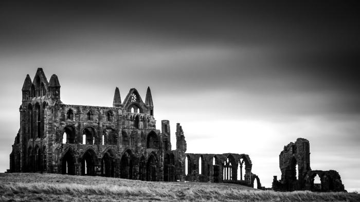 paysage noir et blanc empreint de nostalgie avec une vue sur les ruines de l'abbey whitby en angleterre sur le fond du ciel gris