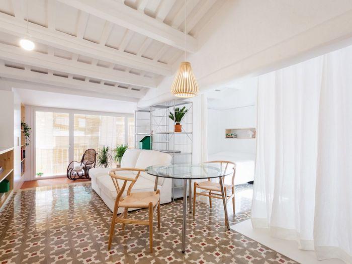 separation chambre à coucher avec rideau transparent, canapé blanc, carrelage original, chaises bois et table en verre et métal, poutres apparentes