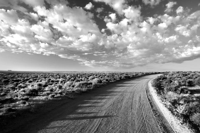 photographie noir et blanc de chemin dans le désert qui se perd dans l'horizon, sous le spectacle des nuages dansant