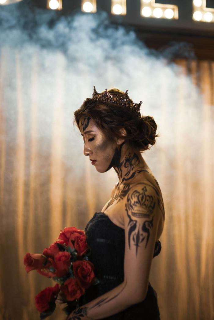 Belle idée de tatouage géométrique stylisé, tatou femme épaule, art tatouage créative, idée pour une femme qui va se marier, couronne et chignon sur les cheveux, robe noire bustier, bouqet de roses rouges