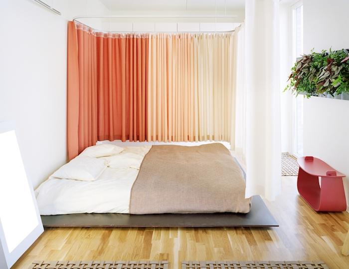 rideaux séparateurs couleur saumon et orange, lit sur plate-forme bois foncé, matelas blanc, couverture de li marron, parquet bois clair, tableau végétal