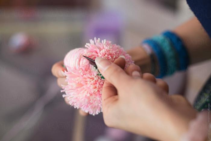 fabriquer un pompon avec ses mains et un ciseau, pompon en fil rose, pompon de laine décoratif