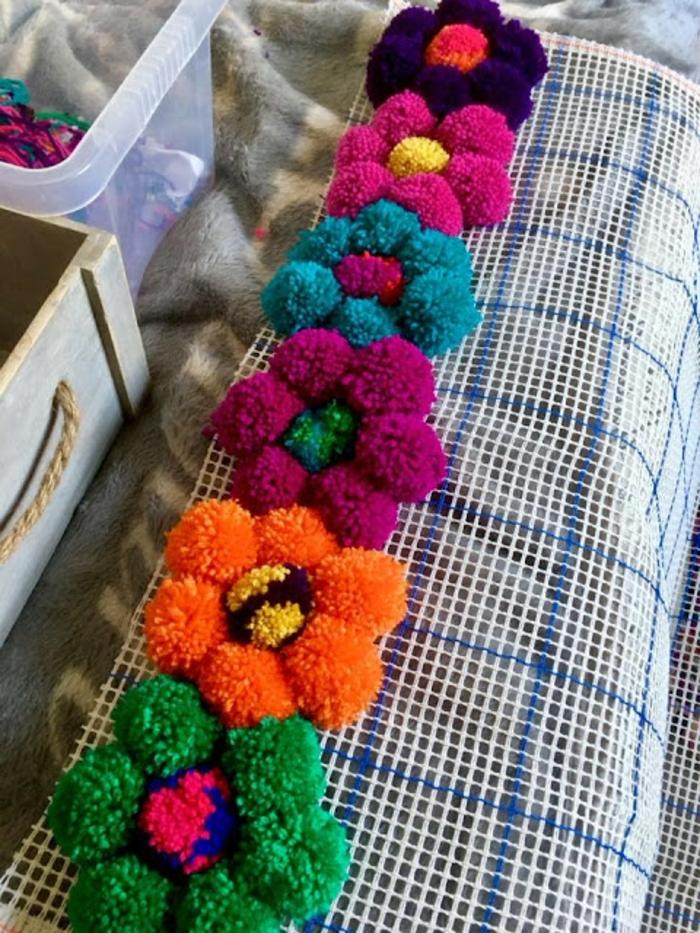 pompons multicolores arrangés en fleurs, diy pompon et diy tapis à réaliser tout seul, toile à canevas pour tapis