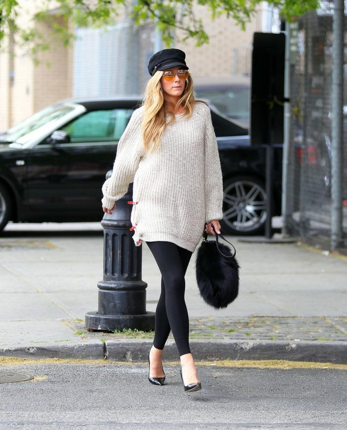 femme portant un sac poilu, grand pull blanc, casquette noire, lunettes tendance, leggings et escarpins