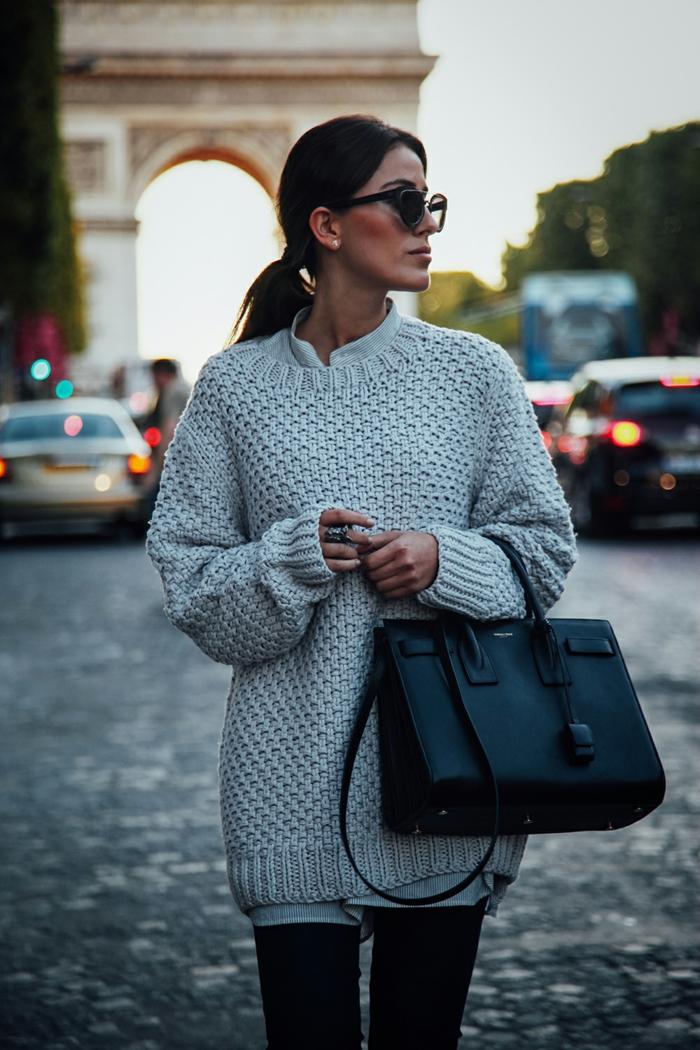 gros sac noir, pull blanc cassé, lunettes de soleil, chemise blanche, queue de cheval basse