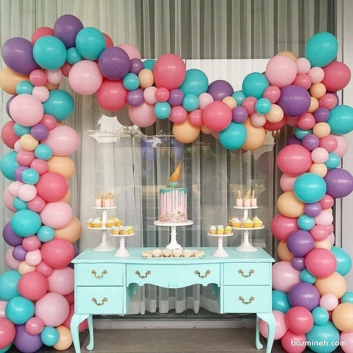 ballons roses et bleus autour d'une commode turquoise, gâteaux cupcakes avec muffins et grand gateau glaçage rose et bleu