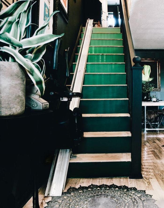 escalier en bois éclectique aux contremarches peintes en dégradé du vert émeraude qui s'harmonisent avec les murs foncés