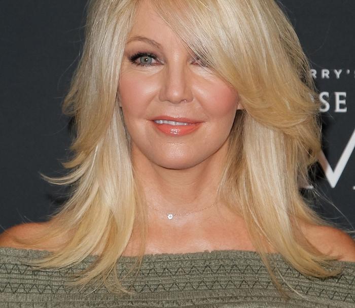 coupe dégradée femme avec des mèches blondes encadrant le visage, longueurs variées d une chevelure volumineuse