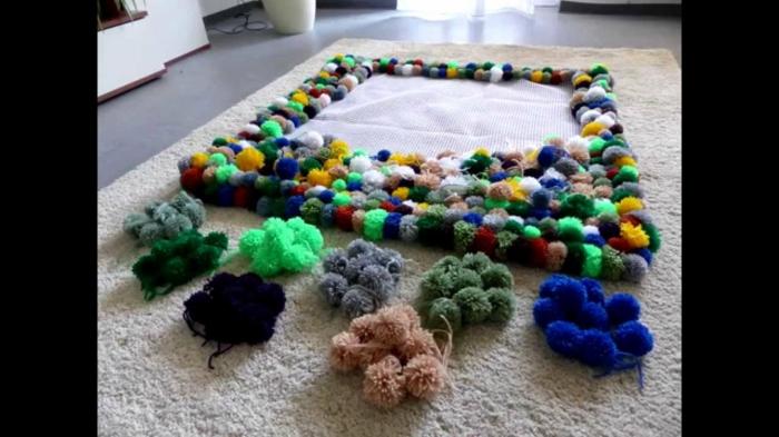 tapis laine multicolore, plusieurs pompons groupés ensembles et liés en tapis diy rectangulaire