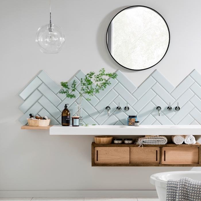 ambiance naturelle et apaisante dans une salle de bains scandinave, crédence salle de bain de carrelage en chevron de couleur vert menthe pâle surmonté d'un miroir rond tendance
