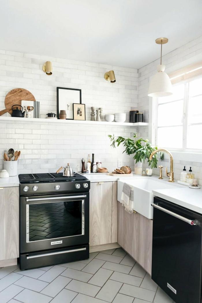 cuisine petite surface, cuisinière noire, évier blanc, robinet doré, étagère blanche, carreaux métro blancs, appliques dorées