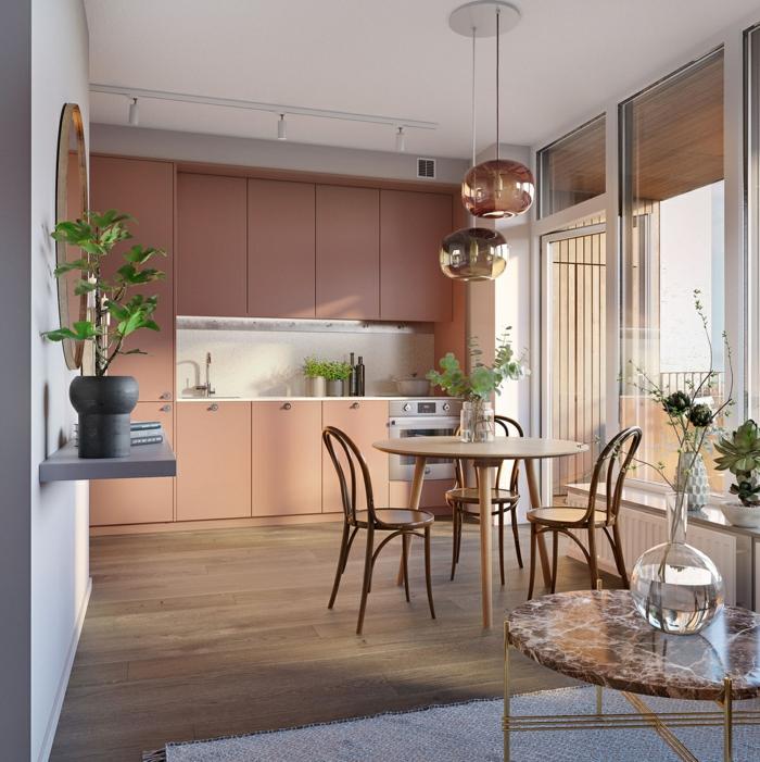 petite cuisine sympathique, portes des placards oranges, lampes cuivrées rondes, table ronde, grand vase en verre avec déco végétale, pot avec arbrisseau