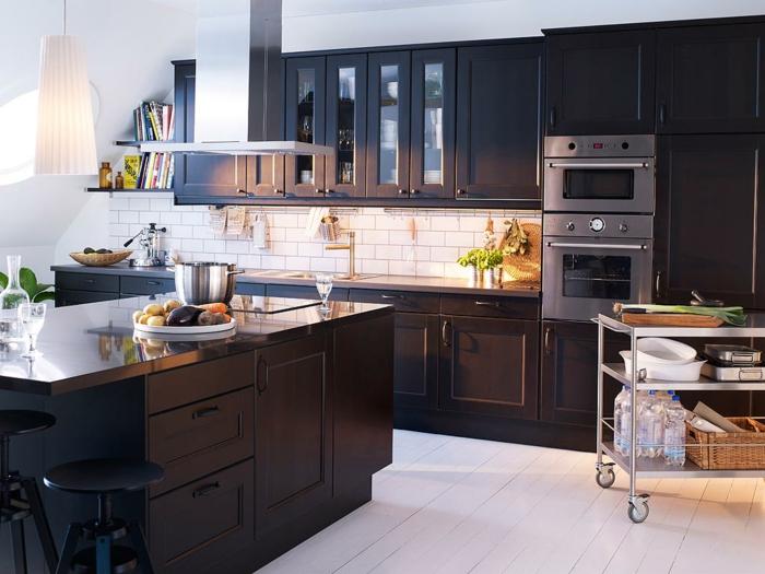 petite cuisine aménagée, rangement de cuisine foncé, sol en planches blanches, chariot de cuisine métallique, robinet doré, îlot avec rangement