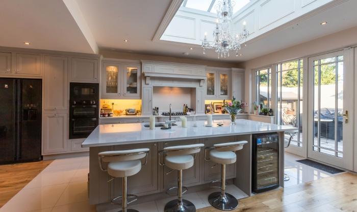 grand ilot de cuisine, chaises de bar aux dossiers, grand puits de lumière, fenêtres du plafond au sol, sol cuisine parquet blanchi