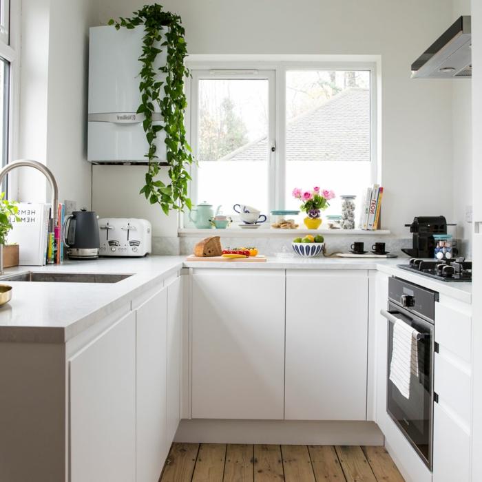 jolie cuisine blanche, sol en bois, placards blancs, évier carré, petit frigo suspendu, étagère blanche sous la fenêtre