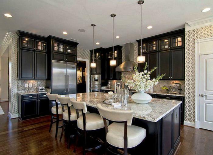 sol en bois laqué, chaises blanches, îlot de cuisine noir comptoir marbré, petites lampes pendantes, placards noirs
